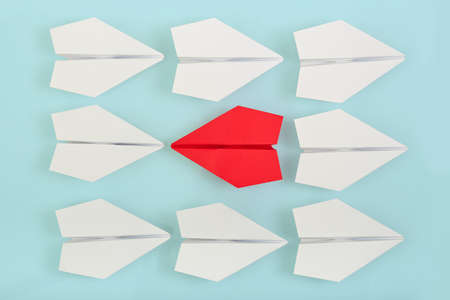 the opposite: being different concept with red paper plane going in a different direction