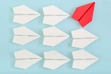 lider: siendo concepto diferente con avión de papel rojo va en una dirección diferente Foto de archivo