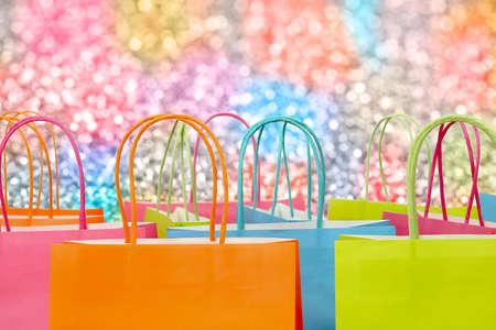 반짝이 배경에 다채로운 종이 쇼핑백