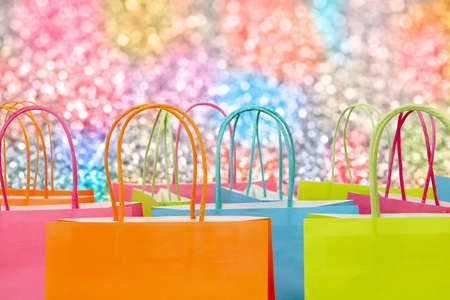 colorful paper shopping bags against glitter background