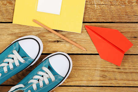 easygoing: sneakers with paper plane and notebook on wooden surface