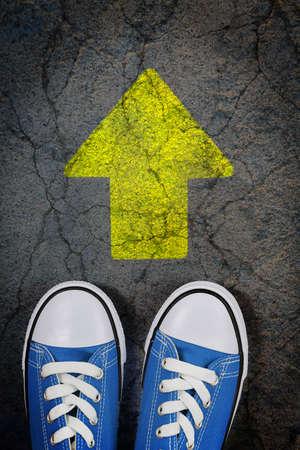 életmód: cipők repedt beton felületén festett nyíl Stock fotó