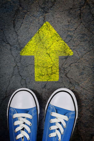 new way: sneakers on cracked concrete surface with painted arrow