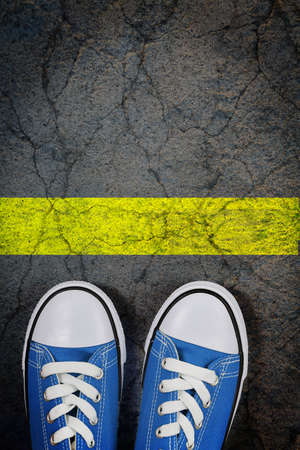 reluctant: sneakers on cracked concrete surface with a painted yellow line Stock Photo