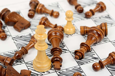 opponents: white chess king surrounded by fallen opponents on hand drawn chessboard