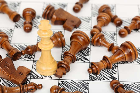 white chess king surrounded by fallen opponents Stock Photo