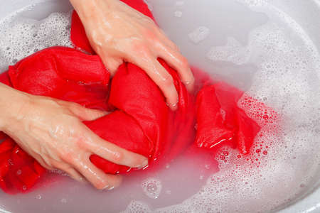 woman washing delicate clothes by hands in plastic tub