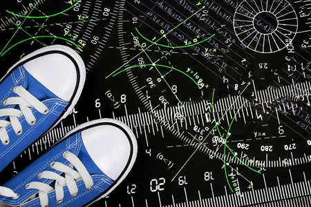 difficult lives: sneakers with rulers and mathematics on black surface, education concept Stock Photo