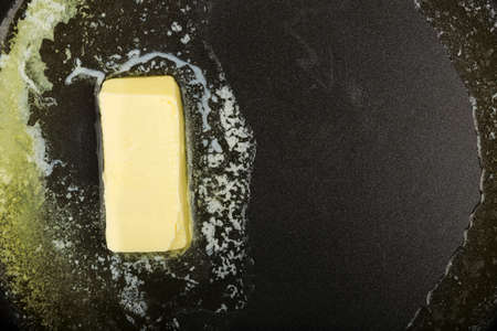 piece of butter while melting in frying pan Imagens - 44248364