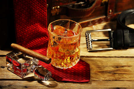 ice chest: elegant glass of whiskey on the rocks and cigar with clothing accessories Stock Photo