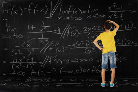 equation: puzzled student looking at a huge blackboard with a difficult equation, school concept Stock Photo
