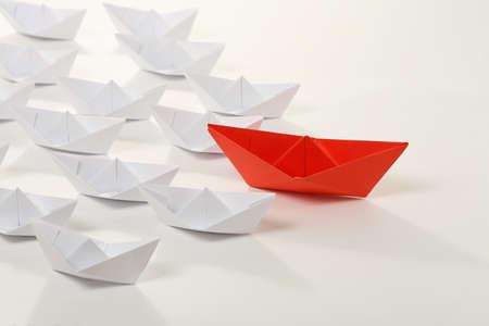 red paper boat leading white ones, leadership concept Reklamní fotografie - 46102627