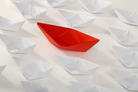 difference: red paper boat among smaller white ones