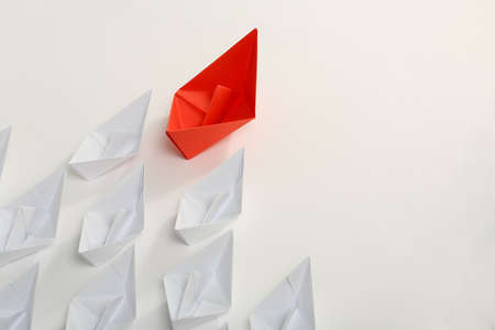 red competition: red paper boat leading white ones, leadership concept