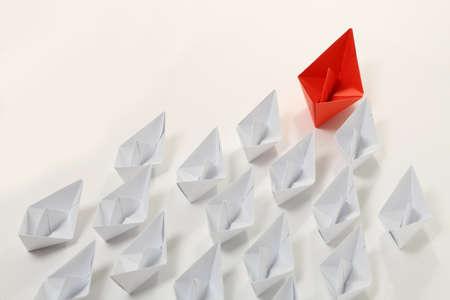 mision: barco de papel de color rojo que lleva las blancas, concepto de liderazgo