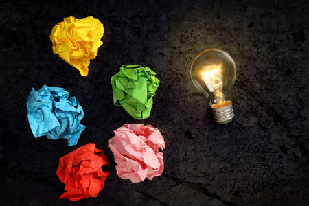 lit lightbulb with crumpled paper balls, idea or inspiration concept Stock Photo