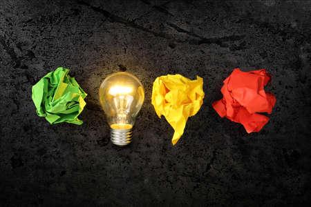 inspiracion: bombilla encendida con bolas de papel arrugado, idea o concepto de la inspiración Foto de archivo