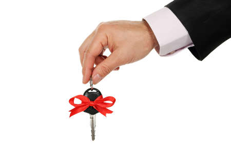 hand key: male hand handing over the key of a new car