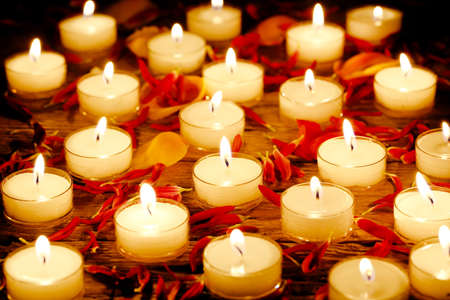 burning candles with flower petals on wooden surface