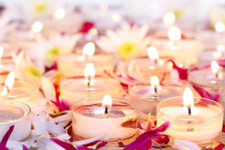 candela: Molte candele che bruciano con petali di fiori viola
