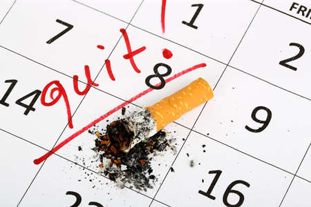 stop: stubbed out cigarette on calendar, quit smoking concept