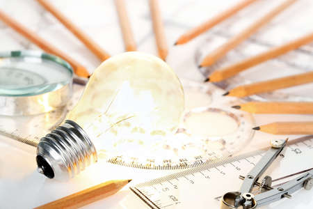 achievement concept: lit light bulb with rulers and pencils on desk, idea concept Stock Photo
