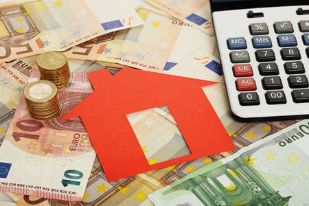 red paper house with euro banknotes and calculator