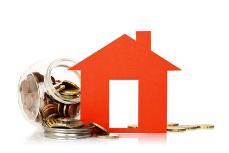 viviendas: casa roja del papel y la jarra con monedas, el concepto de ahorro de casa Foto de archivo