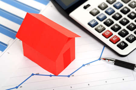 calculadora: rojo casa de papel y calculadora en gr�ficos, el concepto de bienes ra�ces Foto de archivo