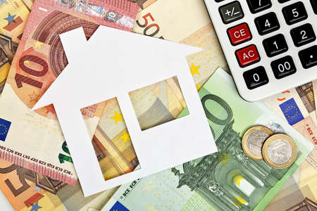 wealth management: paper house with euro banknotes and calculator Stock Photo