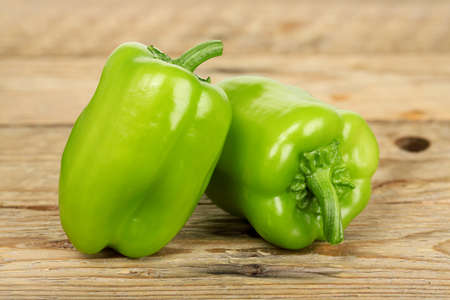 green pepper: two green bell peppers on wooden surface