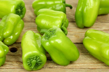 several: several green bell peppers on wooden surface Stock Photo