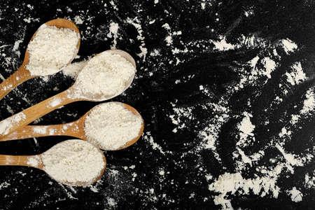 ladles: four wooden ladles of flour on black surface