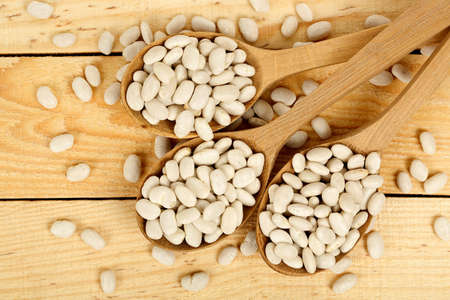 ladles: ladles with dry white beans on wooden planks