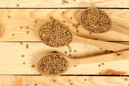 ladles: ladles with raw lentils on wooden planks
