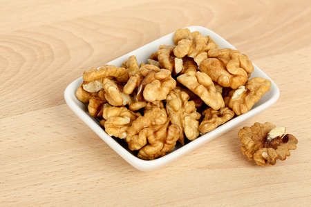 shelled: bowl of shelled walnuts on wooden table