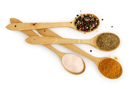 ladles: ladles with pepper, curry, oregano and himalayan salt on white