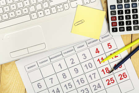 postit: laptop with calendar and calculator on office desk