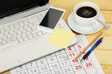 postit: desk office with a laptop, calendar and other objects Stock Photo
