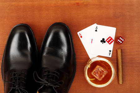 gamblers: shoes with playing cards, dice, cigar and whiskey on wood