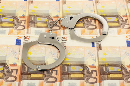 bribery: handcuffs on euro banknotes, corruption, theft or bribery concept Stock Photo