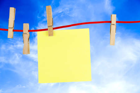 blank note: blank yellow note on clothesline against a blue sky Stock Photo