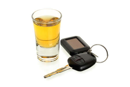 drinking and driving: whiskey shot glass and car keys on white, drinking and driving concept