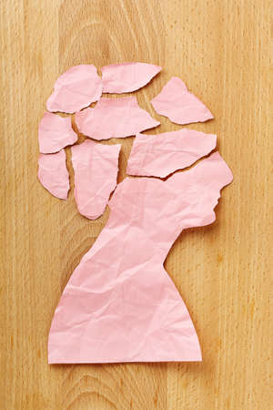 worries: torn and crumpled female paper head on wood, abstract concept