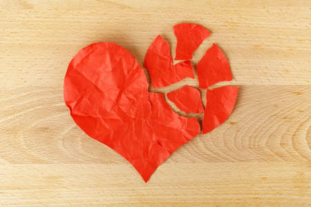 heartbroken: crumpled and torn paper heart on wood, heartbroken concept