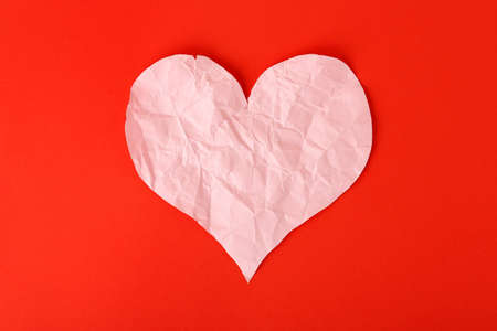 heartbroken: crumpled paper heart on red surface, heartbroken concept