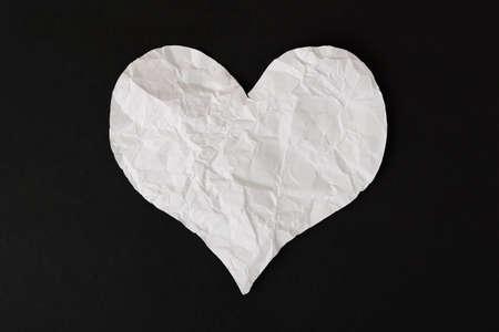white heart: white crumpled paper love heart on black