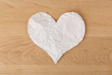heartbroken: white crumpled paper heart on wood, heartbroken concept Stock Photo