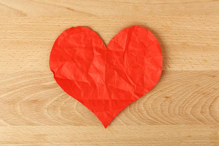 heartbroken: crumpled paper heart on wood, heartbroken concept