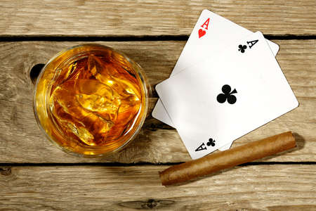 cigar: whiskey with playing cards and cigar on old wooden surface Stock Photo